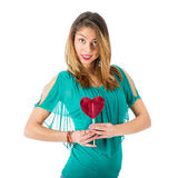 Beautiful woman holding red heart-shaped lollypop in front of her body Royalty Free Stock Photography