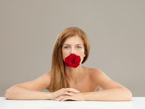 Beautiful woman holding red rose in mouth. Beauty portrait of young, blonde woman, holding a red rose between her teeth Royalty Free Stock Image