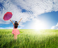 Beautiful woman holding red umbrella in green grass field and cloud sky Stock Photography