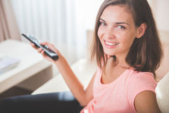 Beautiful woman holding remote control for television Stock Image