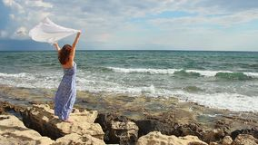 Beautiful woman holding scarf, standing on rocks, strong woman enjoying freedom. Stock footage stock video