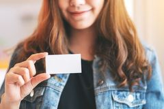A beautiful woman holding and showing a blank empty business card stock photo