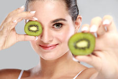 Beautiful woman holding and showing slices of kiwi Stock Photo