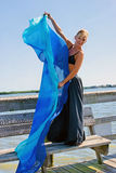 Beautiful woman holding silk. Beautiful blonde dancer is standing on wooden dock bench, looking at viewer and holding a big blue silk cloth, cloth can be used as Royalty Free Stock Photo