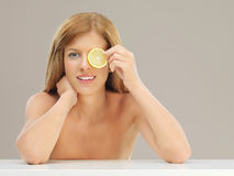 Beautiful woman holding slice of lemon eye Stock Photography
