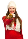 Beautiful woman holding small golden gift. An isolated portrait of a beautiful young woman holding out a small Christmas present. Focus on the present Royalty Free Stock Photos