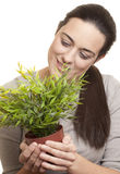 Beautiful woman holding a small plant. With white background stock photography