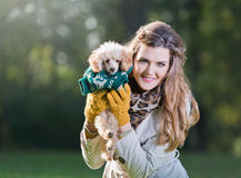 Beautiful woman holding a small poodle. In a park Royalty Free Stock Images