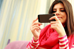 Beautiful woman holding smartphone. Focus on smartphone. Stock Photos