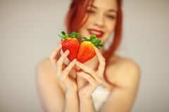 Beautiful woman holding some strawberries in her hands. Sensual studio shot can be used as background royalty free stock images