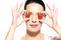 Beautiful woman holding strawberries to her eyes Stock Photos