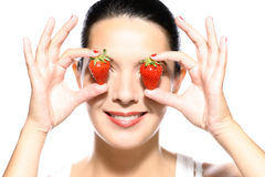 Beautiful woman holding strawberries to her eyes Royalty Free Stock Photos