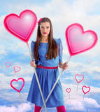 Beautiful woman holding  two hearts. Over a sky background Stock Photo