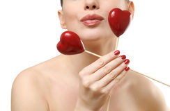 Beautiful woman holding two red hearts. Royalty Free Stock Image