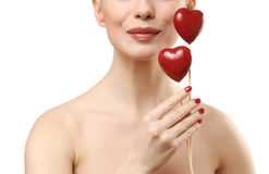 Beautiful woman holding two red hearts. Stock Image