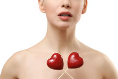 Beautiful woman holding two red hearts crossed. Stock Photos