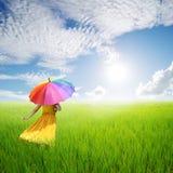 Beautiful woman holding umbrella in green grass field and bule sky. Beautiful woman holding multicolored umbrella in green grass field and bule sky royalty free stock photo
