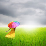 Beautiful woman holding umbrella in green grass field and rainclouds Royalty Free Stock Photography