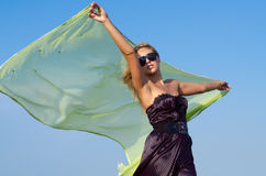 Beautiful woman holding up a green scarf. Beautiful woman in a stylish dress and sunglasses holding up a green scarf to flutter behind her in the breeze Royalty Free Stock Image