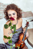 Beautiful woman holding a violin and smelling red rose Royalty Free Stock Photos