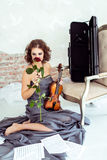 Beautiful woman holding a violin and smelling red rose Royalty Free Stock Images