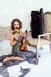 Beautiful woman holding a violin and smelling red rose Stock Photos