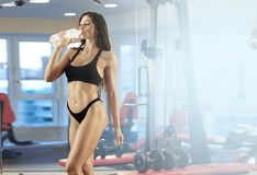 Beautiful Woman holding Water Bottle at Gym and drinks Royalty Free Stock Photos