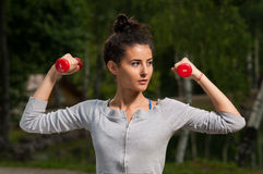Beautiful woman holding weights in her hands Royalty Free Stock Photos