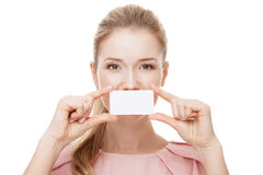 Beautiful woman holding white card at front of her lips. Isolated. Stock Images
