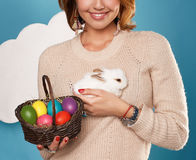 Beautiful woman holding white little Easter bunny basked eggs Royalty Free Stock Photos