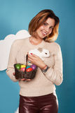 Beautiful woman holding white little Easter bunny basked eggs Royalty Free Stock Images