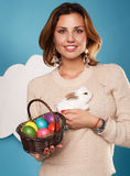 Beautiful woman holding white little Easter bunny basked eggs Stock Images
