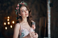 Beautiful woman holding wineglass with rose petals. Celebration concept stock photography