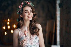 Beautiful woman holding wineglass with rose petals. Celebration concept stock image