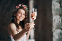 Beautiful woman holding wineglass with rose petals cheers to camera. Focus on wineglass. Celebration concept royalty free stock images