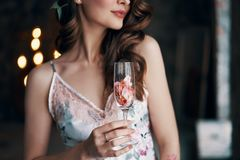 Beautiful woman holding wineglass with rose petals. Focus on wineglass. Celebration, metaphor concept royalty free stock photography
