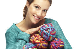 Beautiful woman holding yarn rolls, smiling Stock Image