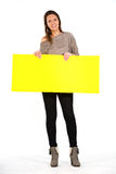 Beautiful woman holding a yellow, blank paper. On white background Royalty Free Stock Photos