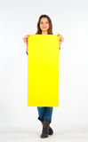 Beautiful woman holding a yellow, blank paper Stock Images