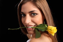 Beautiful woman holding yellow rose in her mouth Stock Image