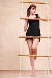 Beautiful woman holds on bamboo rope ladder Royalty Free Stock Photo