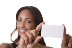 Beautiful woman holds a blank business card. Woman holds a blank business card out in front of her smiling face Stock Photography