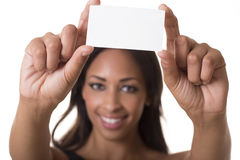 Beautiful woman holds a blank business card. Woman holds a blank business card out in front of her smiling face Stock Images