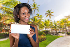 Beautiful woman holds a business card. A beautiful woman with a perfect smile holds a business card Stock Image