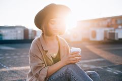 Beautiful woman holds coffee cup on sunset. Attractive young millennial student or fashion model in hipster outfit poses for camera on top of rooftop with sun Stock Photos