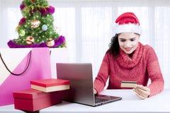 Beautiful woman holds credit card near Christmas tree Royalty Free Stock Photo
