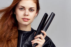 Beautiful woman holds a curling iron on a gray background, hair iron Stock Photo