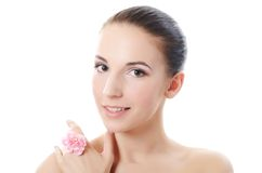 Beautiful woman holds a flower of a carnation at the face Royalty Free Stock Image