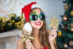 Funny santa girl. Beautiful woman holds gold snowflake, young lady female near big x-mas fir-tree tree, happy New Year party. Sexy santa girl, dreaming about Royalty Free Stock Photo