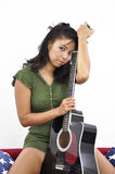 Beautiful woman with guitar between her legs Stock Image